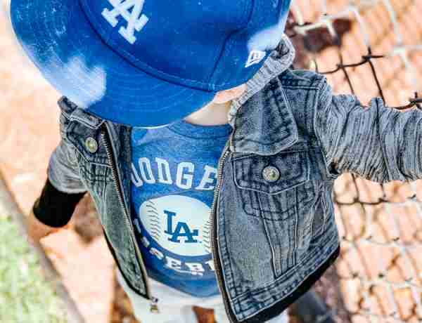 Toddler boy wearing Dodger baseball hat and Dodger baseball shirt standing by back drop of baseball field