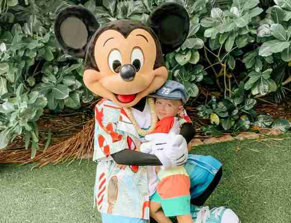 Little boy hugging Mickey Mouse in tropical Hawaii at Aulani