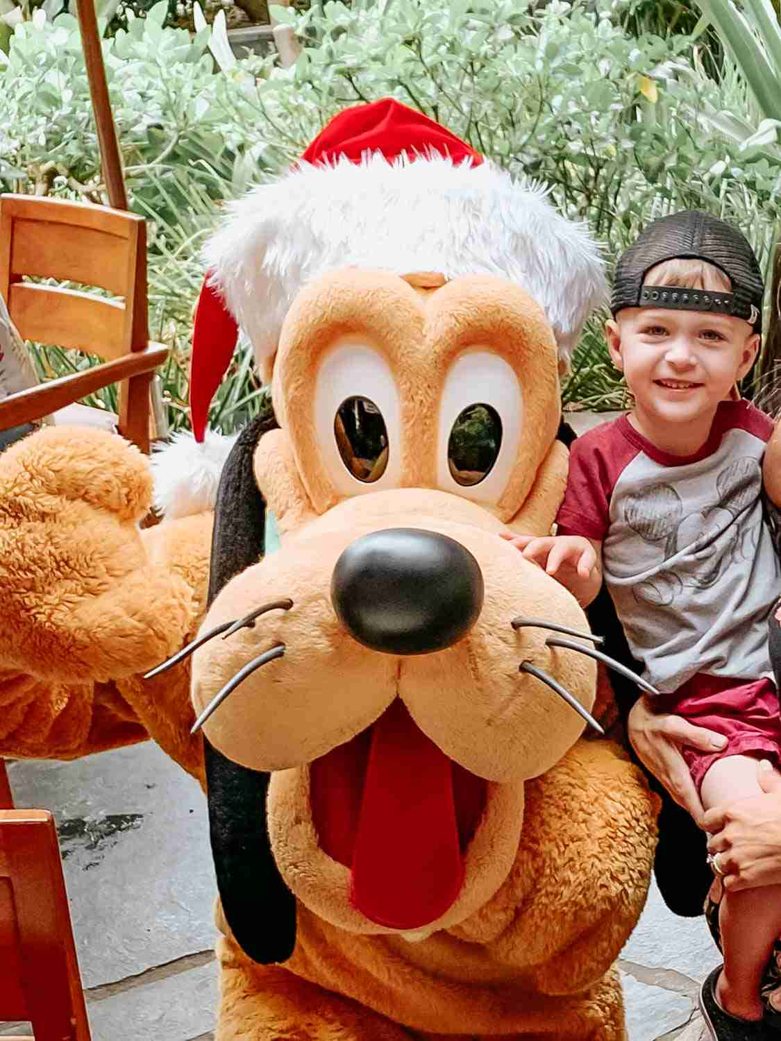 Little boy smiling beside Pluto at the Disney Character Breakfast at Aulani in Hawaii