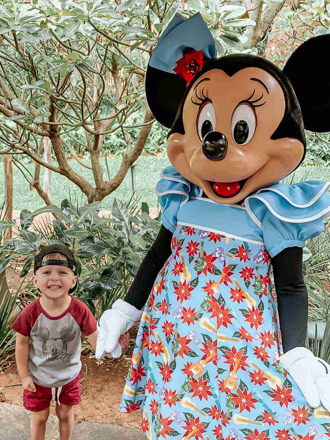 Little boy holding Minnie Mouse's hand at the Disney Character Breakfast at Aulani in Hawaii