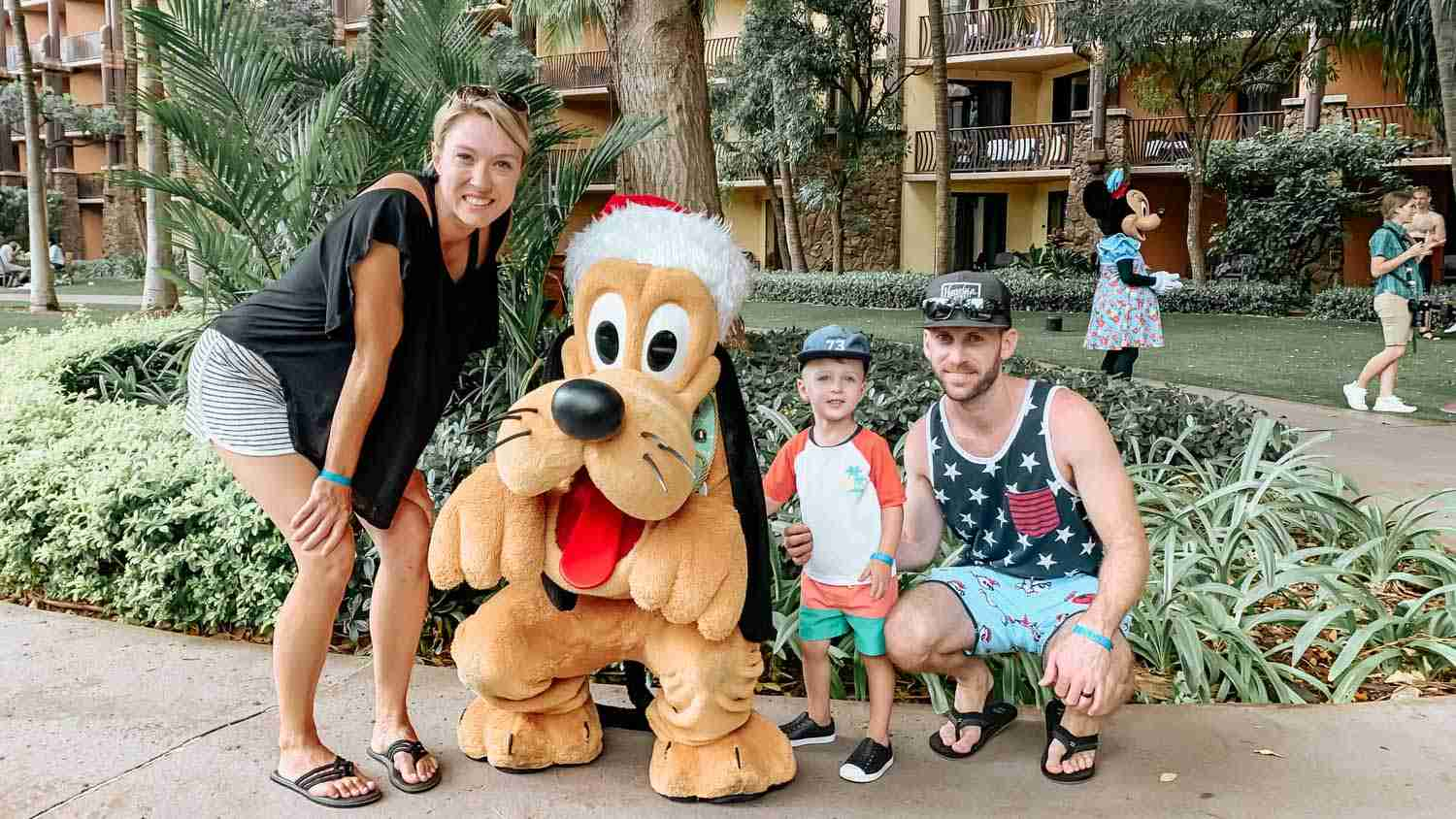 Family smiling with the Disney character Pluto at Aulani in Hawaii