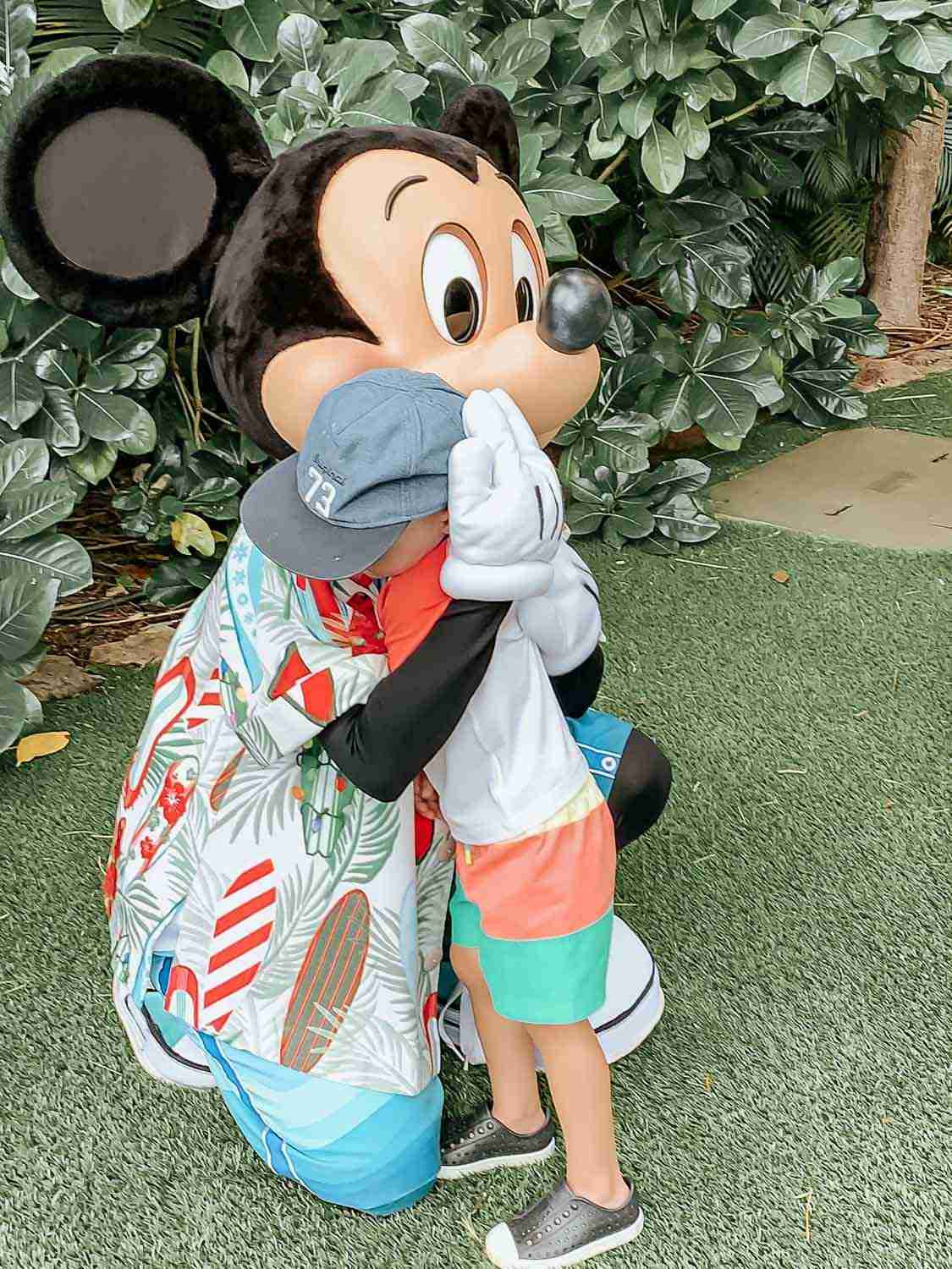 Little boy giving Mickey Mouse a hug at Aulani in Hawaii