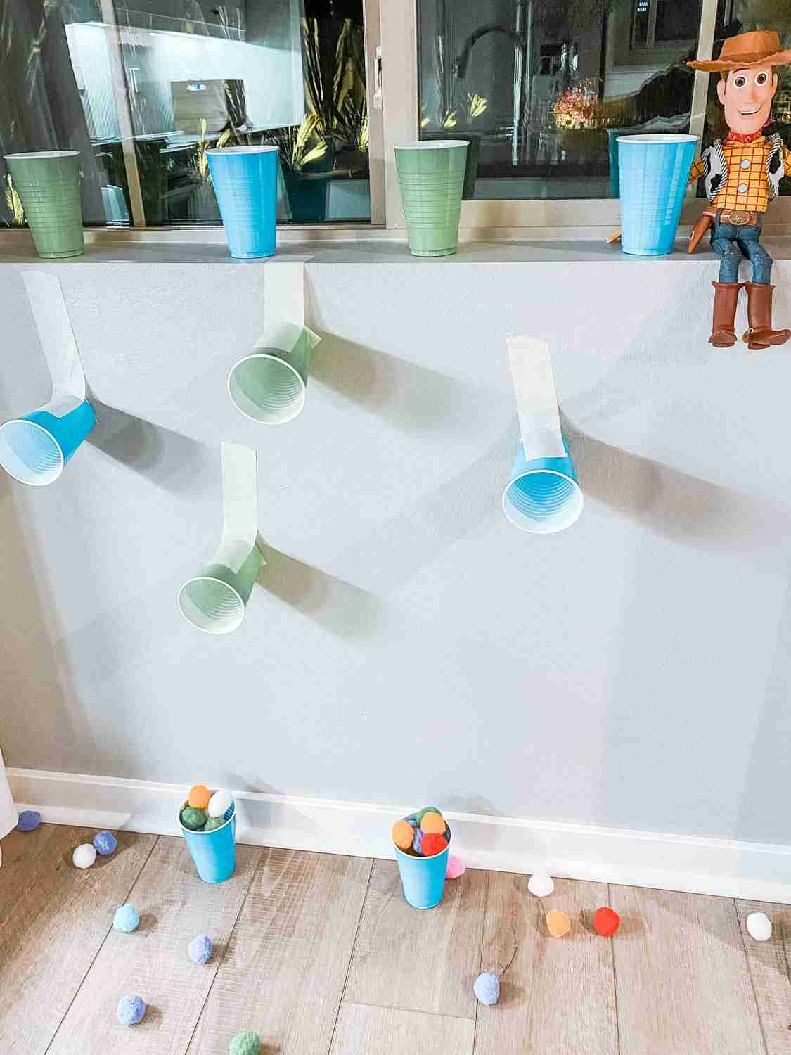 Pom poms and cups set up as Midway Mania game with Woody for Disneyland at home
