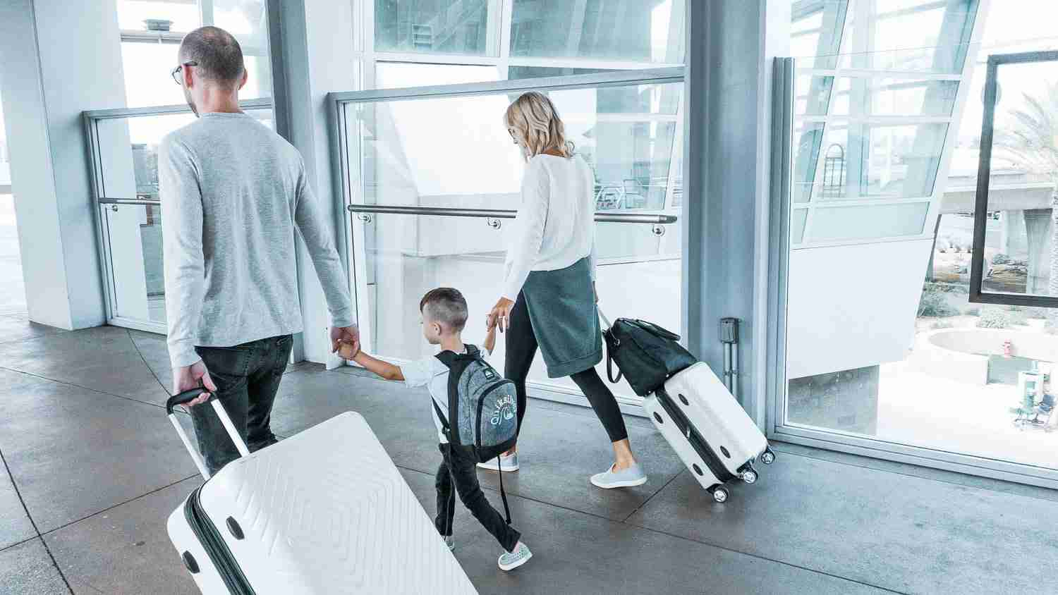 Parents and little boy walking to airport with luggage for minimalist travel