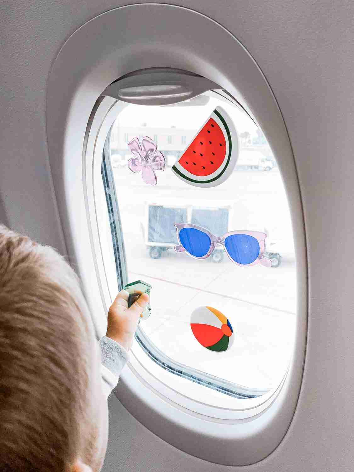 Boy playing with kid's activity gel window clings on airplane window