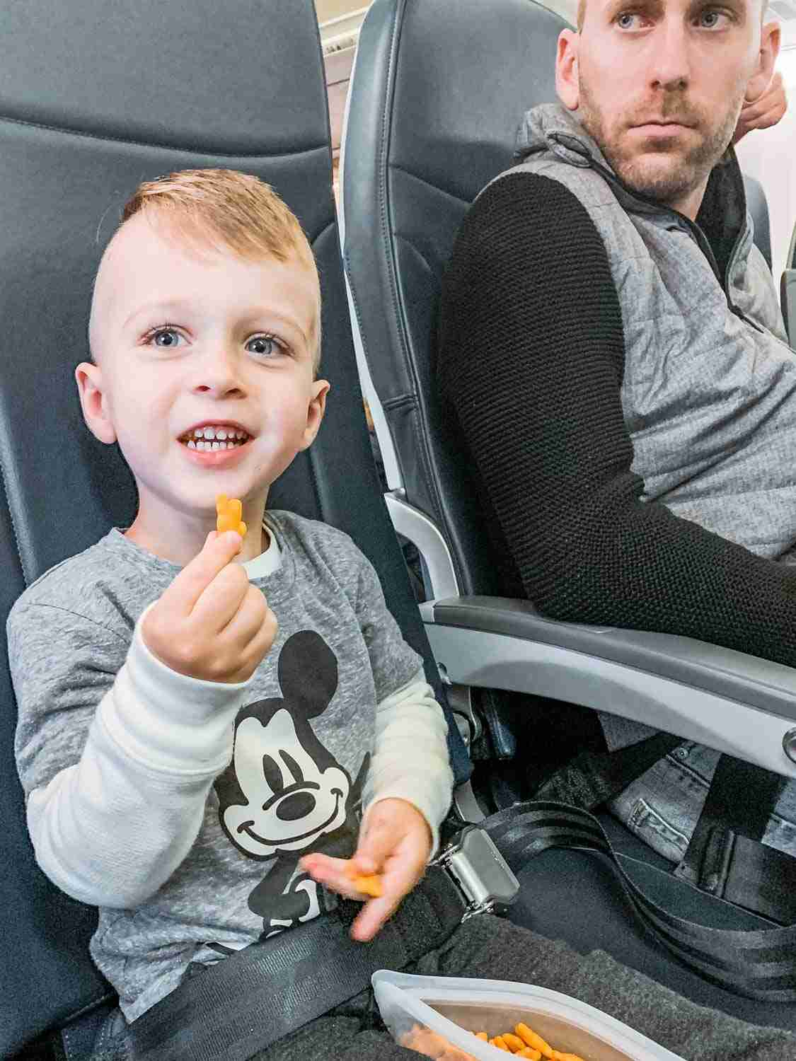 Little boy sitting on plane excited to travel while dad looks unamused about family trip