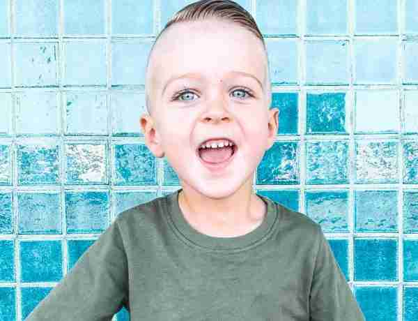 Little boy in front of teal wall excited to go on family trips!