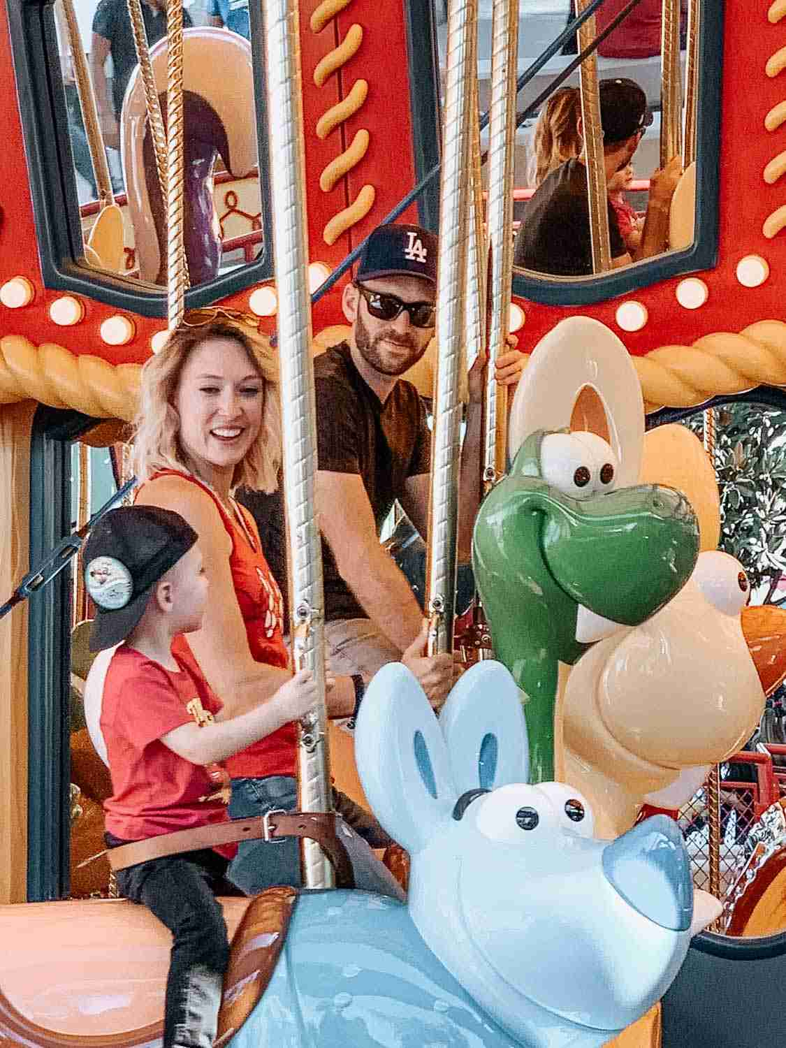Family smiling at each other while riding on Jessie's Critter Carousel at Disney's California Adventure