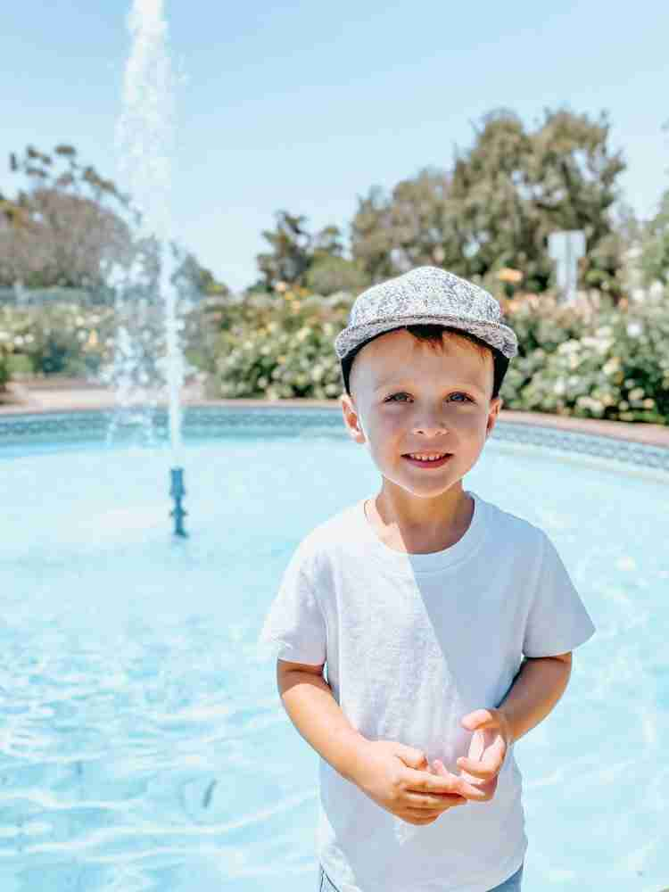 Little boy smiling in front of water fountain