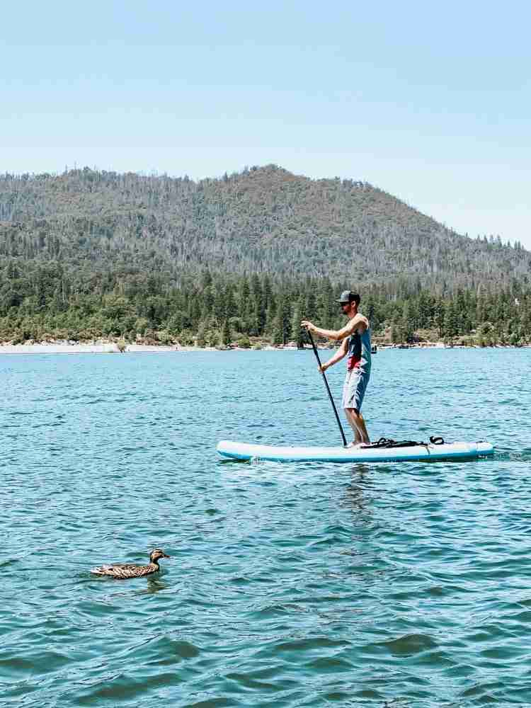 Dad paddle boarding across Bass Lake California