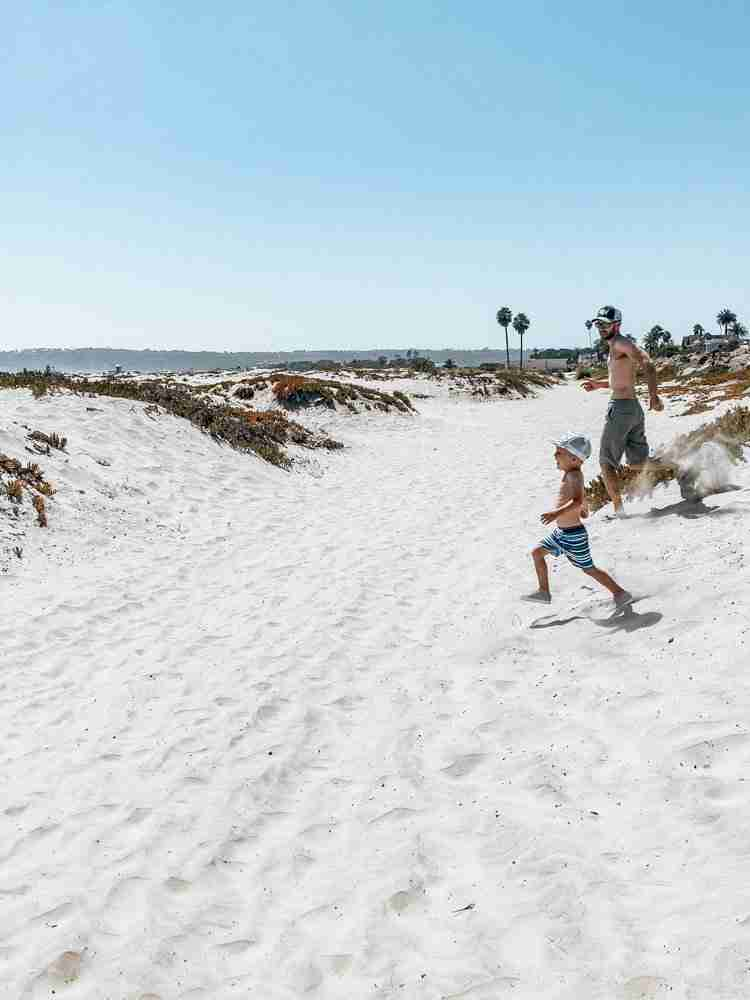Father and son running on sand dunes as one of the things to do on coronado island