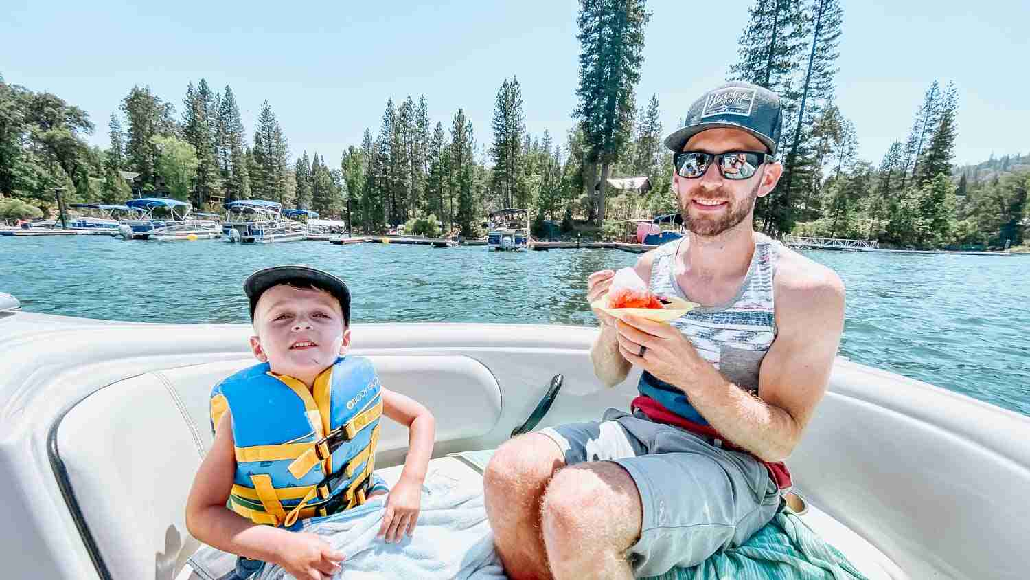 Father and son eating shaved ice on boat on Bass Lake California