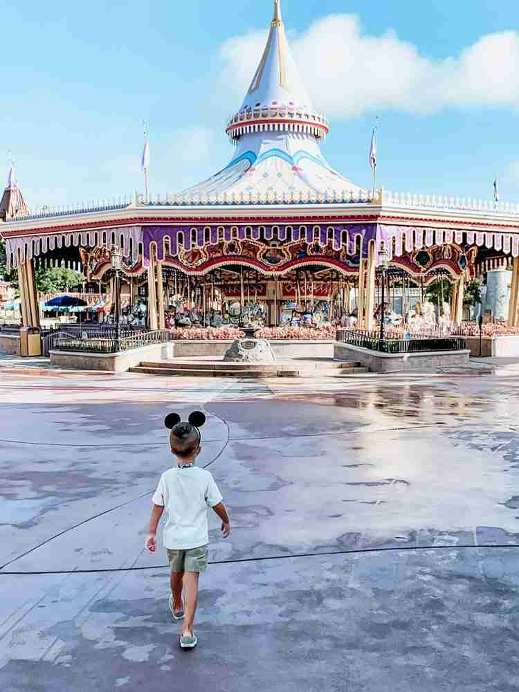Little boy walking into Magic Kingdom as the Disney Parks reopen
