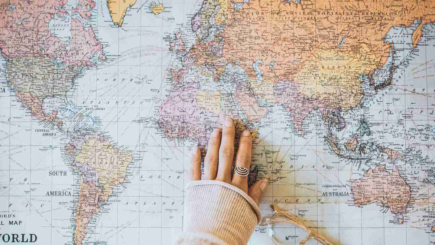 World map with hand placed on it