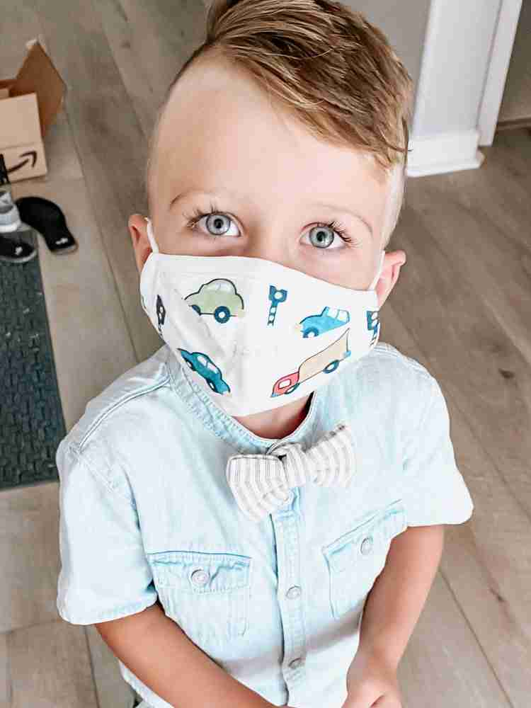 Little boy wearing masks with cars and trucks