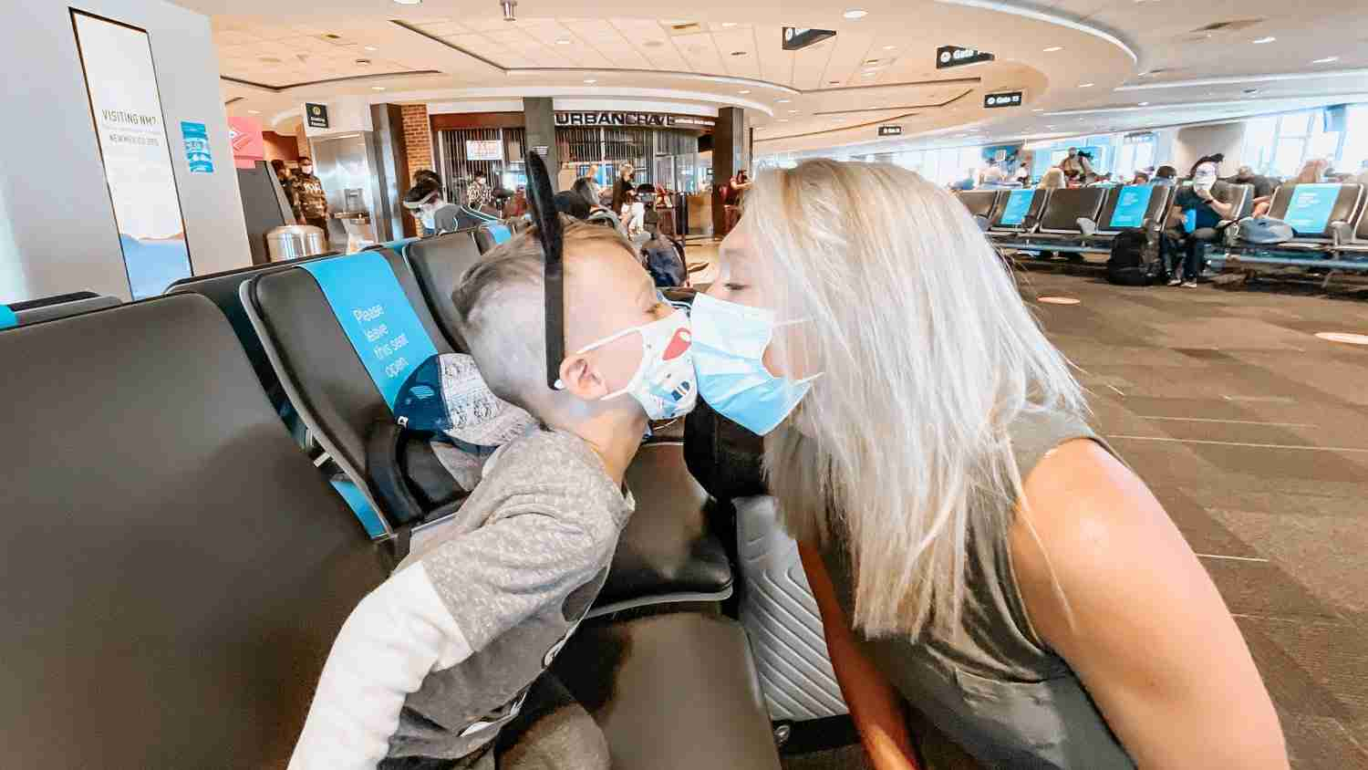 Mom and son wearing masks giving each other a mask kiss