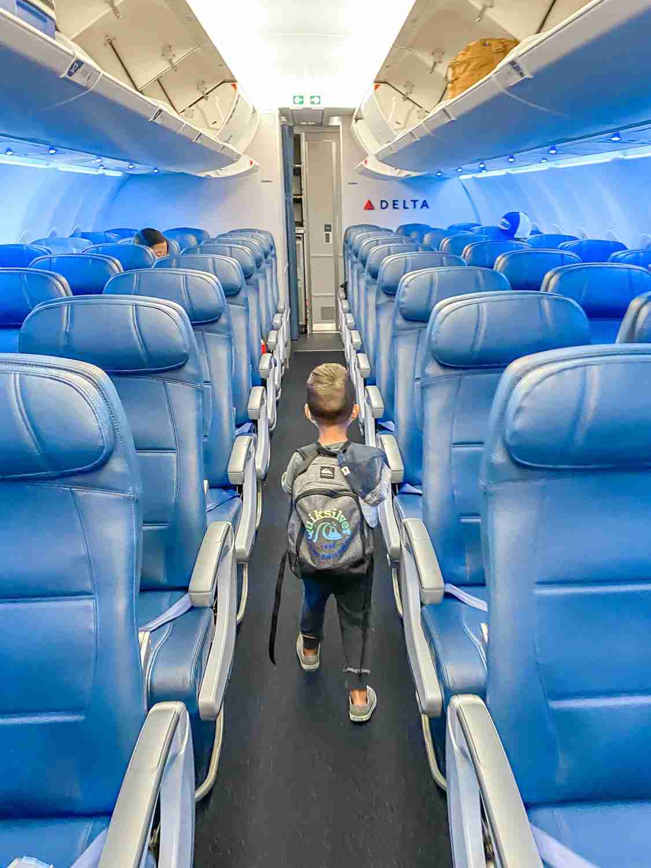 Boy walking down middle aisle of empty plane