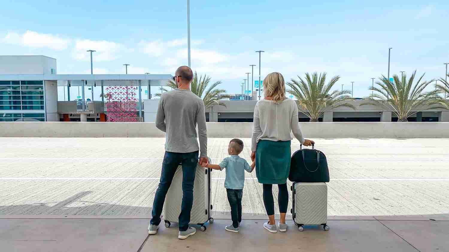Family standing with luggage about to leave on a vacation